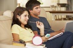 Adolescente y muchacha que se sientan en Sofa At Home Doing Homework que usa el ordenador portátil mientras que sostiene el teléf Foto de archivo libre de regalías