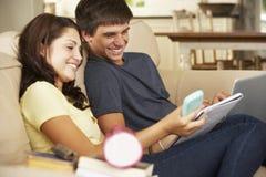 Adolescente y muchacha que se sientan en Sofa At Home Doing Homework que usa el ordenador portátil mientras que sostiene el teléf Fotos de archivo