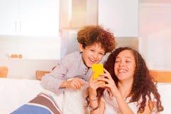 Adolescente y muchacha que tienen Internet que practica surf de la diversión Imagen de archivo libre de regalías