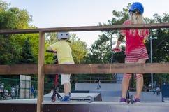 Adolescente y muchacho atractivos en llevar a cabo a su tablero patinador brillante en skatepark Fotos de archivo