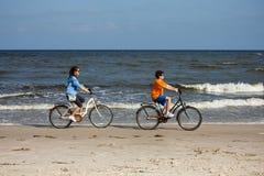 Adolescente y muchacho biking en la playa Fotos de archivo