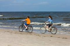 Adolescente y muchacho biking en la playa Imágenes de archivo libres de regalías