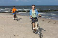 Adolescente y muchacho biking en la playa Fotografía de archivo libre de regalías