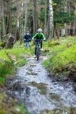 Adolescente y muchacho biking en rastros del bosque Foto de archivo libre de regalías