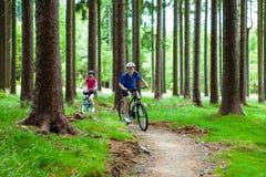 Adolescente y muchacho biking en rastros del bosque Imagen de archivo libre de regalías