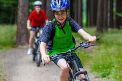 Adolescente y muchacho biking en rastros del bosque Fotos de archivo libres de regalías