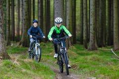 Adolescente y muchacho biking en rastros del bosque Imagenes de archivo