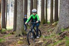 Adolescente y muchacho biking en rastros del bosque Fotos de archivo