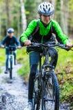Adolescente y muchacho biking en rastros del bosque Foto de archivo