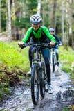 Adolescente y muchacho biking en rastros del bosque Imágenes de archivo libres de regalías