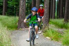 Adolescente y muchacho biking en rastros del bosque Fotografía de archivo