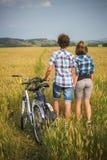 Adolescente y muchacho en una bicicleta en un campo del verano del centeno Imagen de archivo libre de regalías