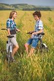 Adolescente y muchacho en una bicicleta en un campo del verano del centeno Fotografía de archivo