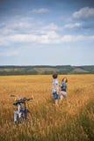 Adolescente y muchacho en una bicicleta en un campo del verano del centeno Fotos de archivo libres de regalías