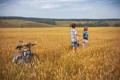 Adolescente y muchacho en una bicicleta en un campo del verano del centeno Imagenes de archivo