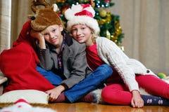 Adolescente y muchacho sonrientes que se sientan en el piso con un árbol de navidad en fondo Imagen de archivo