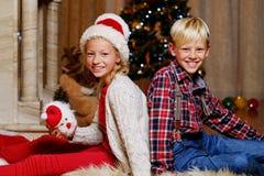 Adolescente y muchacho sonrientes que se sientan en el piso con un árbol de navidad en fondo Foto de archivo