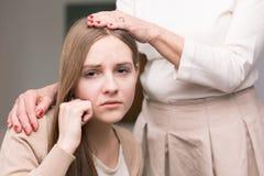 Adolescente y mujer tristes con la mano en su cabeza Fotografía de archivo