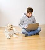 Adolescente y ordenador portátil y perro Fotografía de archivo libre de regalías