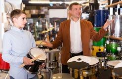 Adolescente y padre que deciden sobre unidad de tambor en tienda musical Foto de archivo libre de regalías