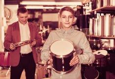 Adolescente y padre que deciden sobre unidad de tambor en tienda musical Imagen de archivo libre de regalías