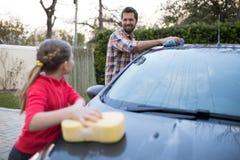 Adolescente y padre que lavan un coche Imagenes de archivo