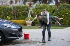 Adolescente y padre que lavan un coche Fotos de archivo