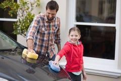 Adolescente y padre que lavan un coche Fotos de archivo libres de regalías