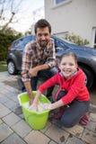 Adolescente y padre que lavan un coche Fotografía de archivo libre de regalías