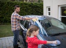 Adolescente y padre que lavan un coche Imágenes de archivo libres de regalías