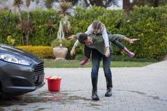 Adolescente y padre que lavan un coche Foto de archivo