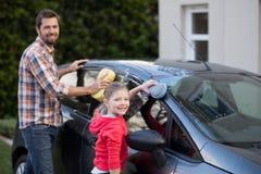 Adolescente y padre que lavan un coche en un día soleado Foto de archivo libre de regalías