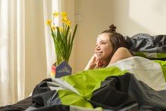 Adolescente y ramo de flores amarillas de la primavera Cama del fondo en el cuarto Foto de archivo libre de regalías