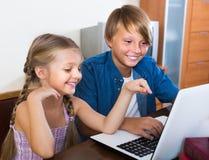 Adolescente y su hermana que juegan al juego en línea Imágenes de archivo libres de regalías