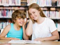 Adolescente y su hermano con los libros Foto de archivo