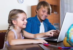 Adolescente y su Internet que practica surf de la pequeña hermana Foto de archivo libre de regalías