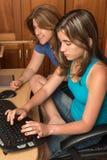 Adolescente y su madre al lado de un ordenador Foto de archivo libre de regalías