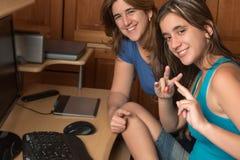 Adolescente y su madre al lado de un ordenador Fotos de archivo