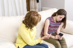 Adolescente y su madre tenga una discusión sobre su teléfono en casa Foto de archivo