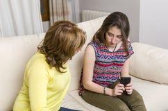 Adolescente y su madre tenga una discusión sobre su teléfono en casa Imagenes de archivo