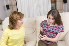 Adolescente y su madre tenga una discusión sobre su teléfono en casa Fotos de archivo libres de regalías