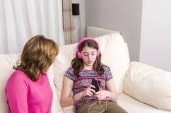 Adolescente y su madre tenga una discusión sobre su teléfono en casa Imágenes de archivo libres de regalías