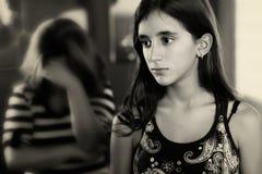 Adolescente y su madre triste que lloran en el fondo Imagen de archivo libre de regalías
