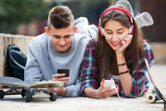 Adolescente y su novia con smartphones Foto de archivo libre de regalías