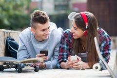 Adolescente y su novia con smartphones Imágenes de archivo libres de regalías