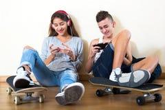 Adolescente y su novia con smartphones Fotos de archivo