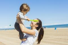 Adolescente y su pequeño hermano que juegan en la playa Imagen de archivo libre de regalías