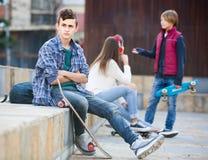 Adolescente y sus amigos después del conflicto al aire libre Foto de archivo libre de regalías