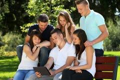 Adolescente y tableta del grupo Foto de archivo