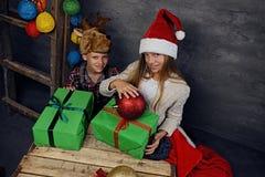 Adolescente y una muchacha en el sombrero del ` s de Papá Noel que presenta con las cajas de regalo Imágenes de archivo libres de regalías